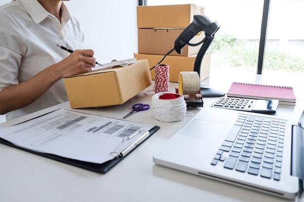 起業家の中小企業は注文クライアントを受け取り、包装ソートボックス配達オンライン市場での作業