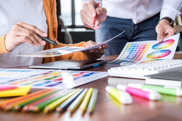 Два коллеги креативный графический дизайнер работают над выбором цвета и рисованием на графическом планшете