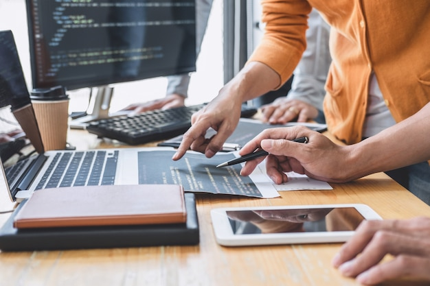 Программист сотрудничает, работая над проектом веб-сайта в разработке программного обеспечения на компьютере в компании.