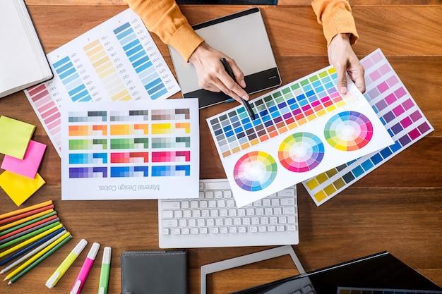 Изображение креативного графического дизайнера, работающего над выбором цвета и нанесением на графический планшет