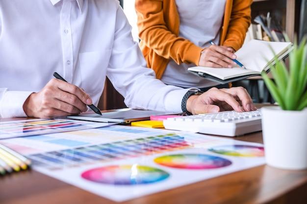 Два креативных графических дизайнера работают над подбором цветов и образцов, рисуя на графическом планшете