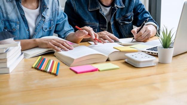 Концепция образования, преподавания, обучения, технологии и людей. два старшеклассника или одноклассники вместе помогают другу делать домашние задания в классе, читают книги с друзьями