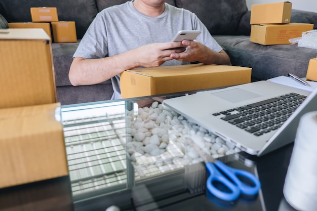 若い起業家中小企業のフリーランスの男が注文をしてスマートフォンを使用してオンラインビジネス