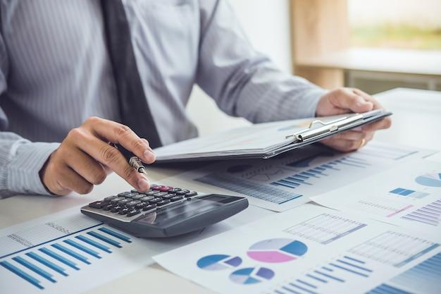 Деловой человек или бухгалтер, работающий с финансовыми вложениями в калькулятор