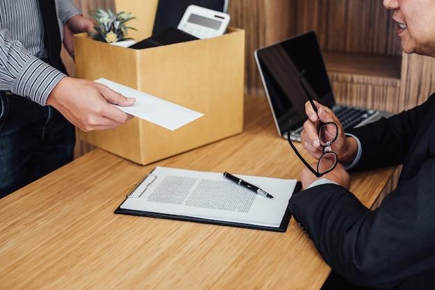 ビジネスマンの手紙をダンボール箱を保持し、彼の上司に辞表手紙を送る
