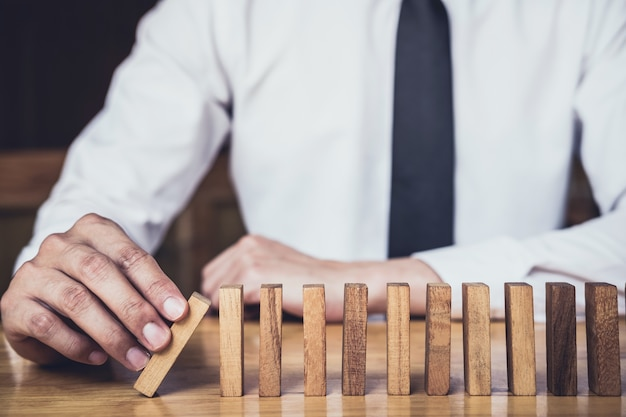 ビジネスマンの手を止め続ける落ち込んだ木製のドミノ効果