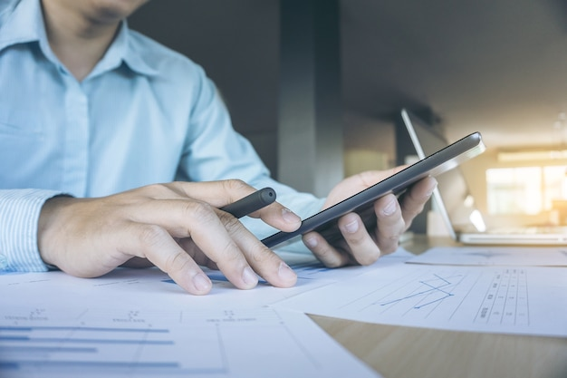 Руки делового человека с помощью планшета с большим количеством графиков и ноутбуков утром