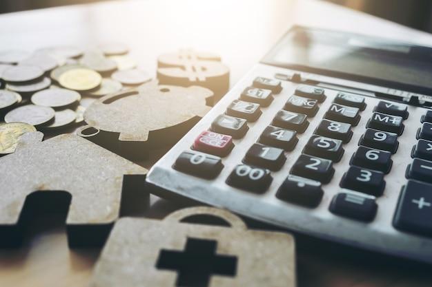 お金、電卓、医療、豚と家のモデルとビジネスの背景