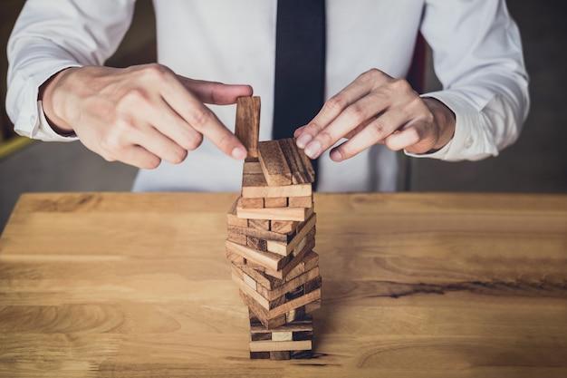 タワーに木ブロックを置いて引っ張るビジネスマンの手の画像
