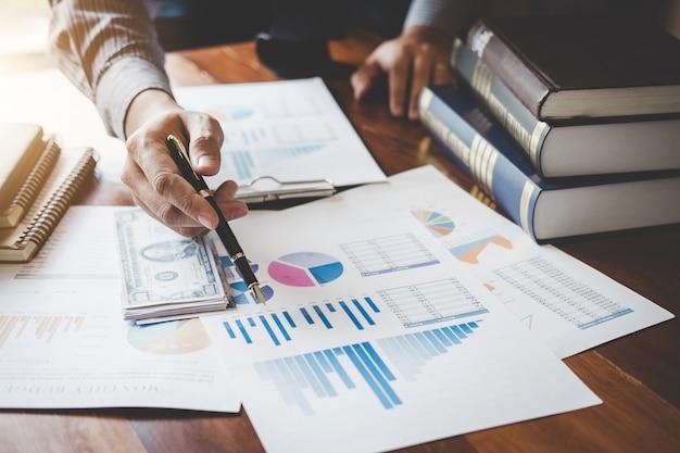 Бизнесмен, указывая на график и диаграмму, чтобы использовать анализ для планов по улучшению качества