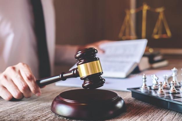 Мужчина-юрист или судья, работающий с юридическими книгами, молоток и баланс, доложит дело