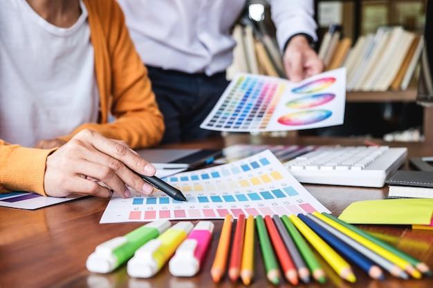 Два коллеги креативного графического дизайнера работают над выбором цвета и образцами цветов