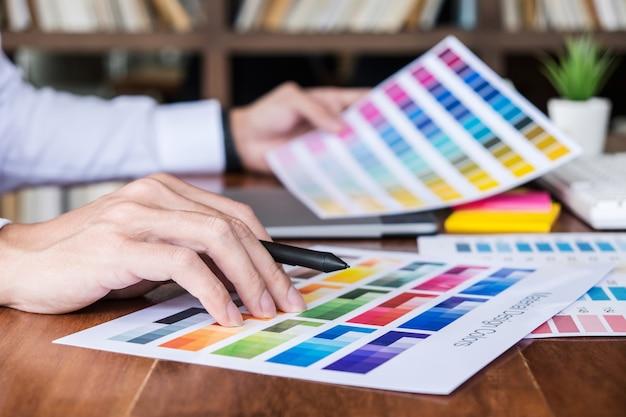 Креативный графический дизайнер, работающий над выбором цвета и нанесением на графический планшет