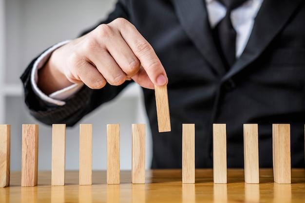 Крупным планом руки бизнесмена, азартные игры, поместив деревянный блок на линии домино