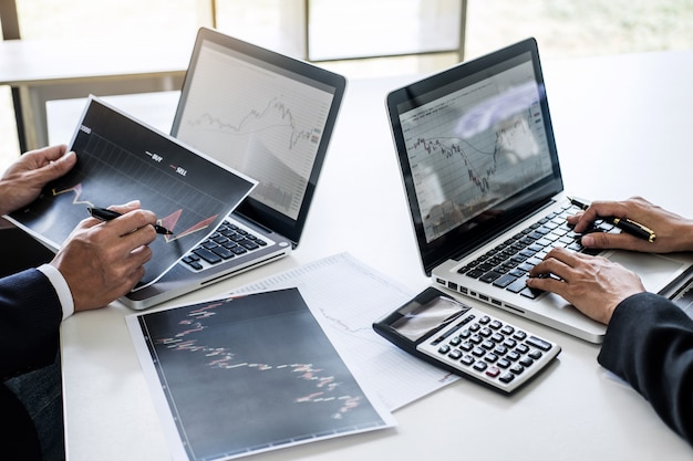 Бизнес команда работает с компьютером, ноутбуком, обсуждения и анализа графика биржевой торговли