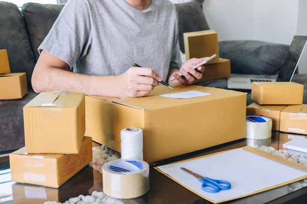 若い起業家の中小企業のフリーランスは、注文のクライアントを受け取り、発注書にパッケージの並べ替えボックスの配信オンライン市場での作業メモを取ります