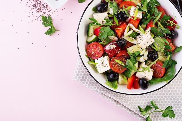 Греческий салат с огурцом, помидорами, сладким перцем, листьями салата, зеленым луком, сыром фета и оливками с оливковым маслом