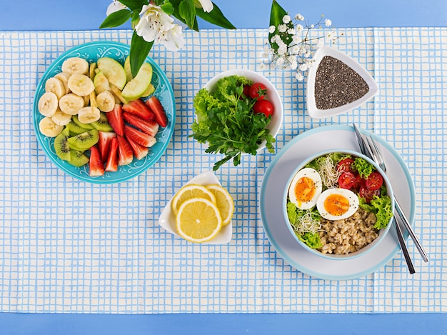 オートミール、トマト、レタス、マイクログリーン、ゆで卵、フルーツプレートのフレッシュサラダ