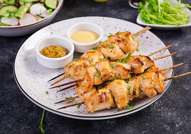 Жареный куриный шашлык и салат с огурцом, редисом и луком
