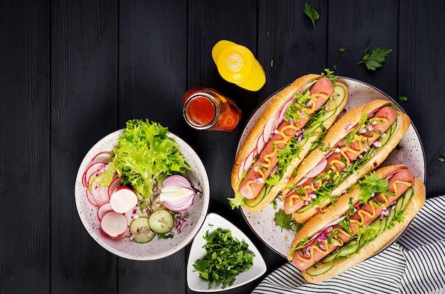 Хот-дог с колбасой, огурцом, редисом и салатом
