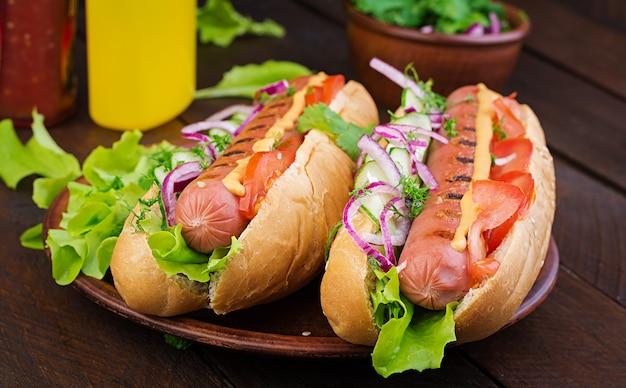 Хот-дог с колбасой, огурцом, помидором и салатом