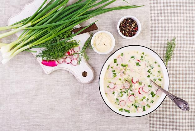 Холодный суп со свежими огурцами, редисом, картофелем и колбасой с йогуртом в миске