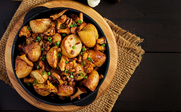 Запеченный картофель с чесноком, зеленью и жареными лисичками в чугунной сковороде