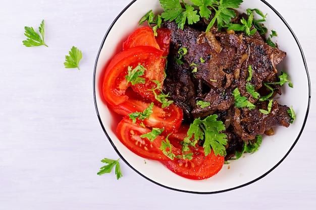Жареная или жареная говяжья печень с луком и салатом из помидоров