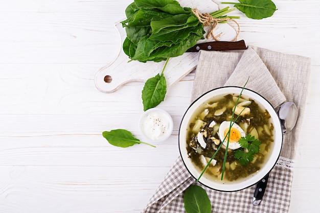 Зеленый суп из щавеля в белой миске