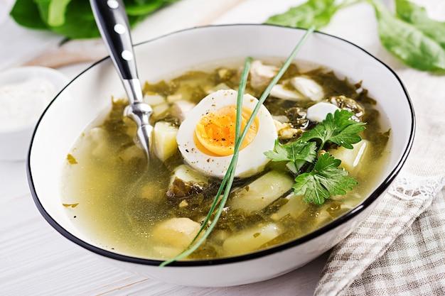 白いボウルにスイバの緑のスープ