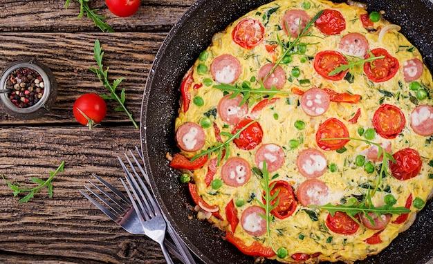 素朴なスタイルのトマト、ソーセージ、グリーンピースのオムレツ