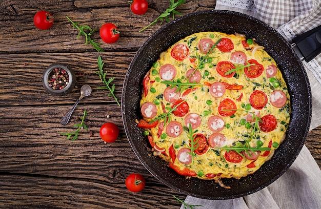素朴なスタイルのトマト、ソーセージ、グリーンピースのオムレツ。フリッタータ-イタリアのオムレツ。上面図