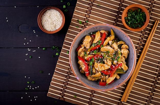 Обжарить курицу, цуккини, сладкий перец и зеленый лук с палочками для еды