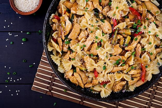 Обжарить курицу, пасту фарфалле, цуккини, сладкий перец и зеленый лук