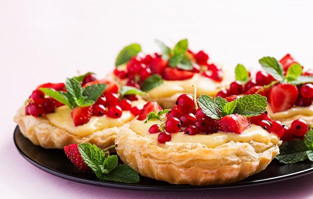 ミントの葉で飾られたイチゴ、スグリ、ホイップクリームのタルト