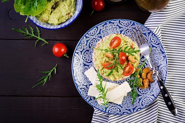 Полезные тосты из авокадо на завтрак, гуакамоле, оливки каламата, помидоры, орехи кешью и сыр фета