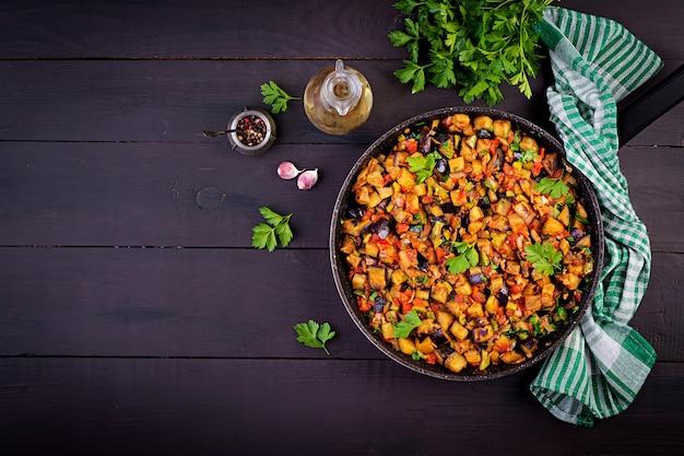 Вегетарианские тушеные баклажаны, сладкий перец, лук, чеснок и помидоры с зеленью