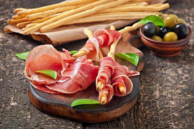 グリッシーニのパンスティック、ハム、オリーブ、バジル、古い木製