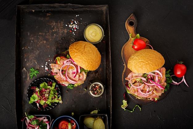 Гамбургер с говядиной, помидорами, маринованным огурцом и жареным беконом.