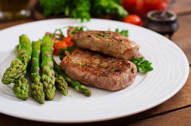 バーベキューグリルビーフステーキ肉とアスパラガスとトマト。