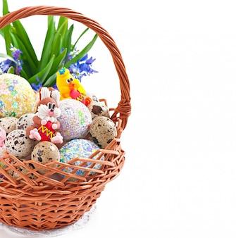 Красочные пасхальные яйца в корзине на белом