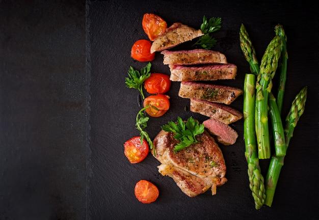 Сочный стейк средней редкости из говядины со специями и помидорами, спаржей.