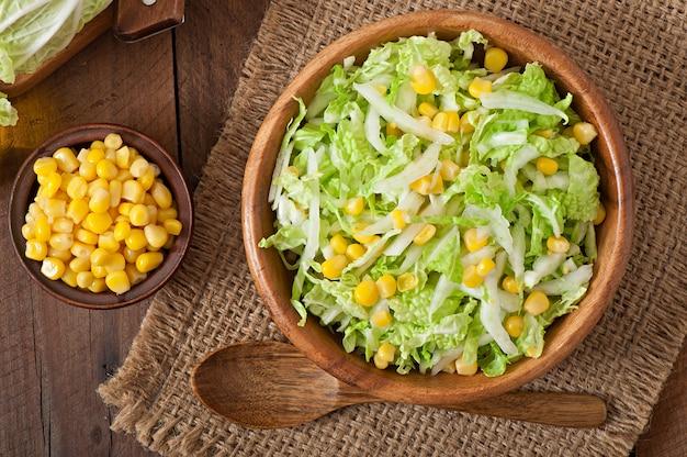 Салат из китайской капусты со сладкой кукурузой в деревянной миске