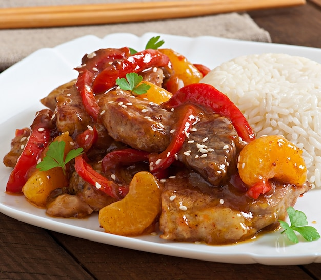 Мясо в остром соусе, сладкий перец и мандарины с гарниром из отварного риса