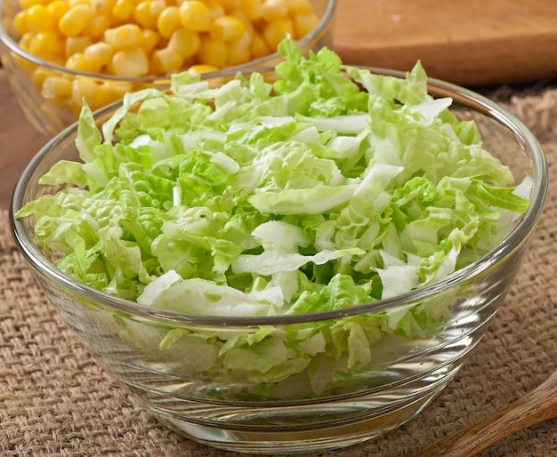 Салат из китайской капусты со сладкой кукурузой в стеклянной миске
