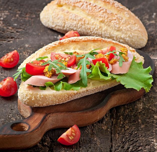 古い木製の背景にソーセージ、レタス、トマト、ルッコラのサンドイッチ