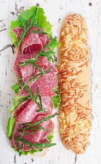 Бутерброд с салями, листьями салата, помидорами и рукколой