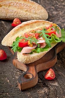 Бутерброд с колбасой, листьями салата, помидорами и рукколой на старых деревянных фоне