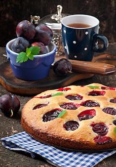 Вкусный домашний торт со сливами на деревянном фоне
