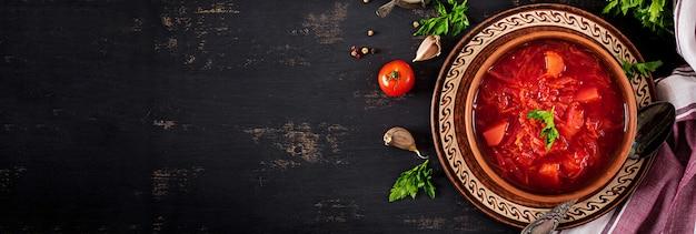 伝統的なウクライナのロシアのボルシチまたはボウルの赤いスープ。バナー。上面図